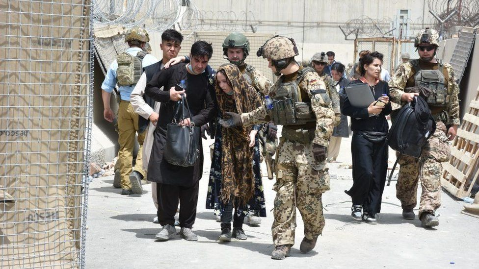Soldiers help a women, fell due to high temperature at the Kabul International Airport