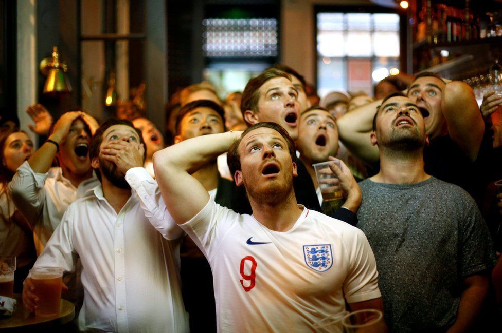 England fans react as they watch the match in London