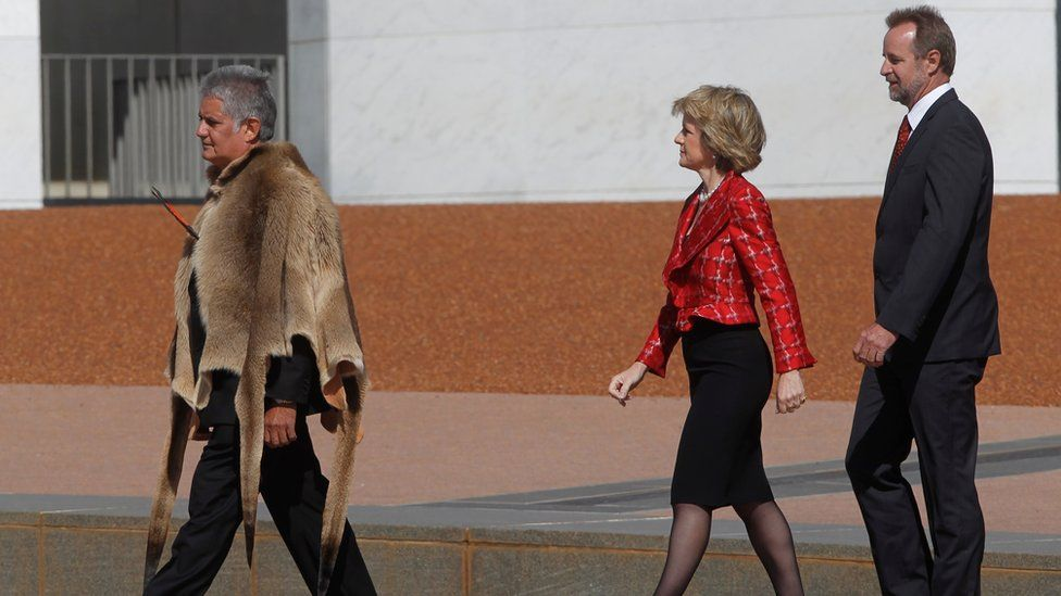 Ken Wyatt wearing a traditional Indigenous kangaroo skin coat walks in front of Liberal MPs Julie Bishop and Nigel Scullion outside parliament house in 2010
