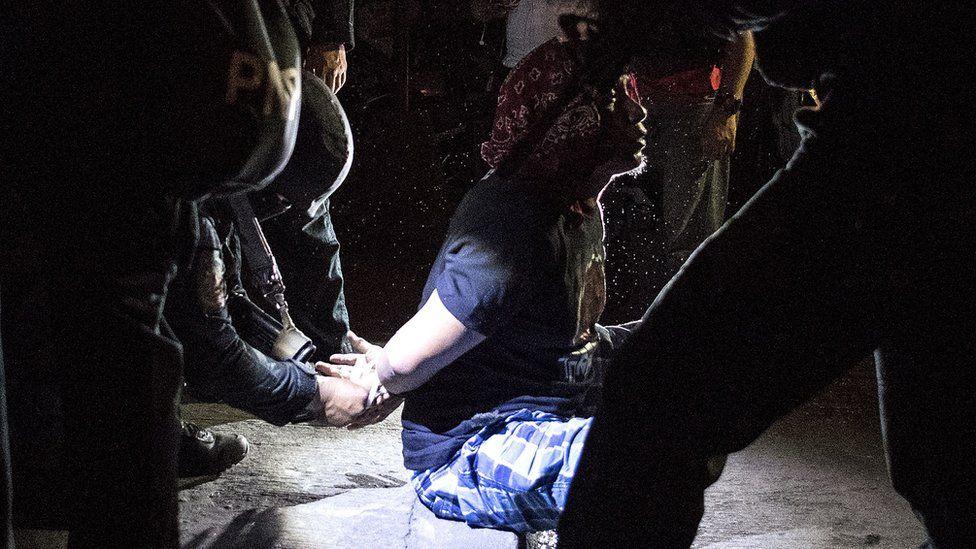 An alleged drug dealer is arrested during a raid in Maharlika Village, Taguig, south of Manila