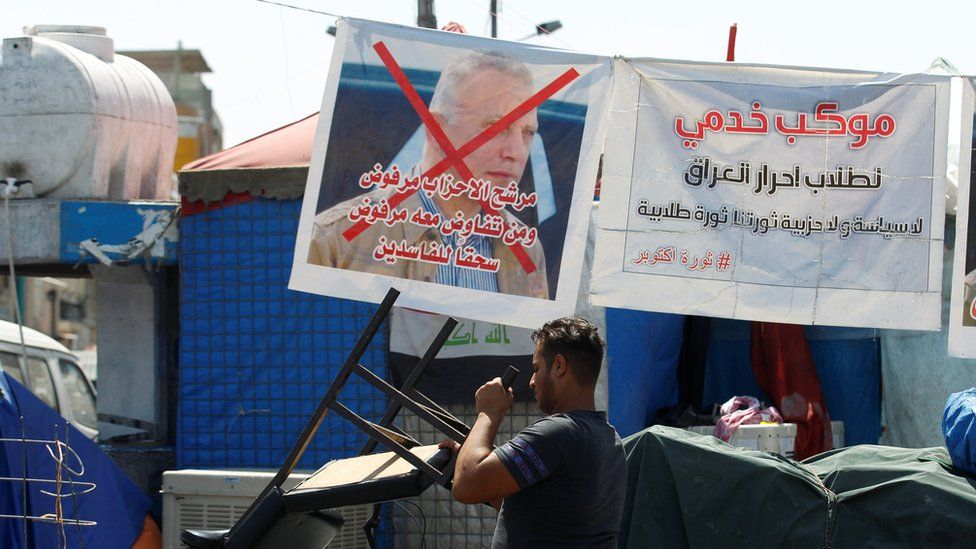 An Iraqi protester walks past a poster rejecting new Prime Minister Mustafa al-Kadhimi in Tahrir Square, Baghdad, Iraq (7 May 2020)