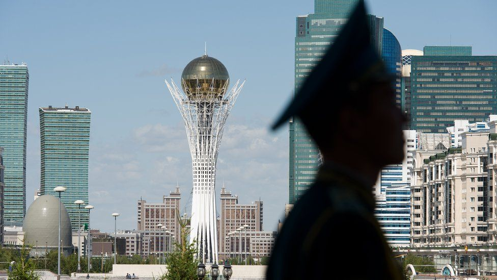 A soldier stands guard with a view of the Kazakh capital Astana in the background.