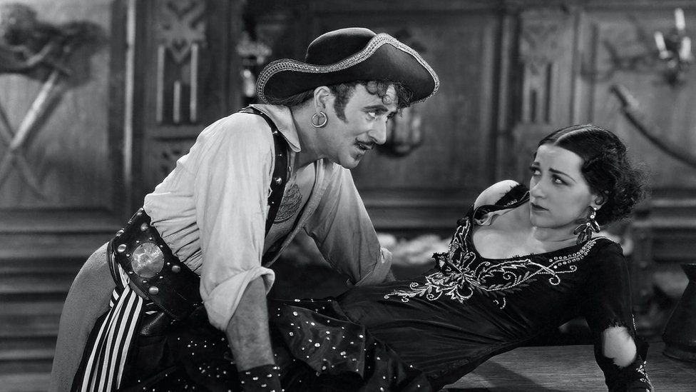 A still from a 1920s pirate film showing a male pirate menacing a woman