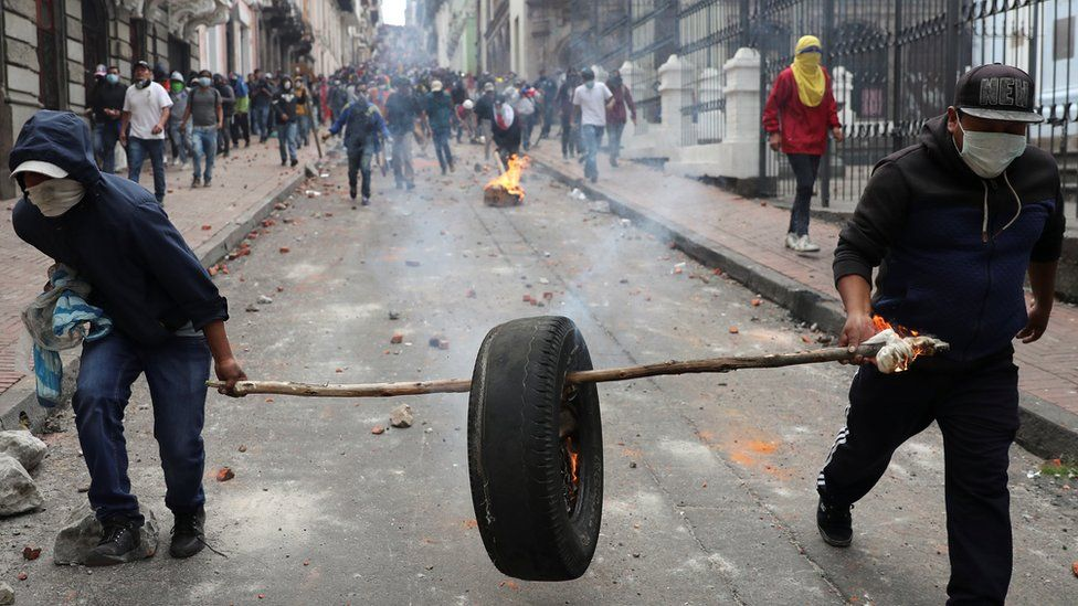 Protesters carry a burning tyre down a road strewn with rocks