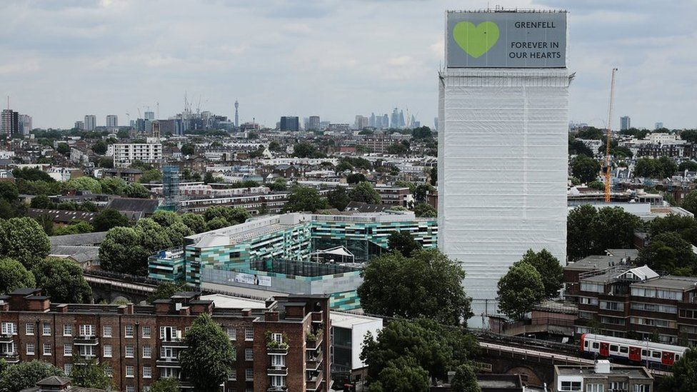 "A sign with ""Grenfell Forever In Our Hearts"" is displayed on the top of Grenfell Tower"