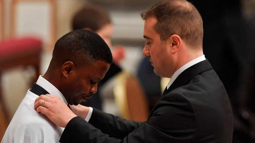 Nigerian John Ogah (L), 31, stands in front of his godfather Italian carabinieri Nunzio Carbone (R), after being baptised by Pope Francis in the Vatican.
