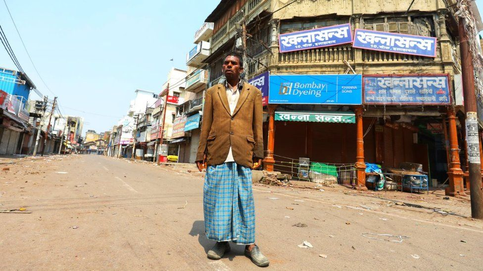 Kishan Lal stands in an empty street the northern Indian city of Allahabad,