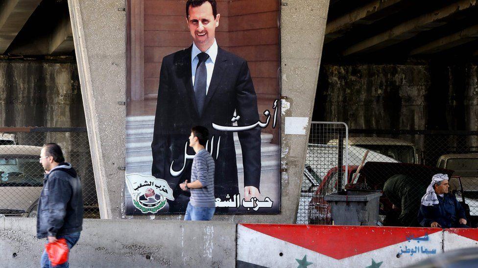 Syrian men walk past a poster bearing a portrait of President Bashar al-Assad in Damascus