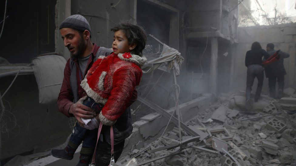 A man holds a child after an air strike in the besieged town of Douma, in the Eastern Ghouta, Syria (7 February 2018)