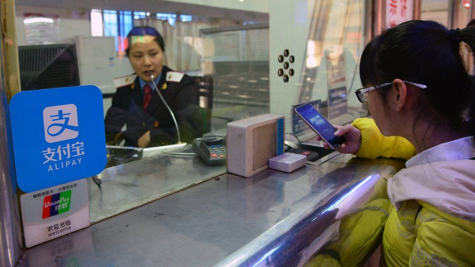 A student pays her travel fare using Alibaba's Alipay app