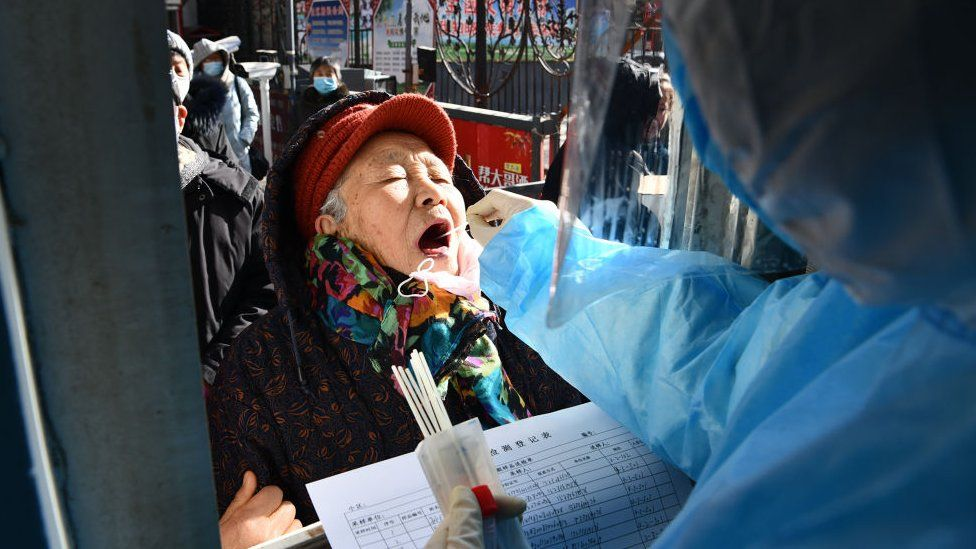 This photo taken on January 6, 2021 shows a medical worker taking a swab sample from a woman outside a residential compound following a new outbreak of the Covid-19 coronavirus in Shijiazhuang