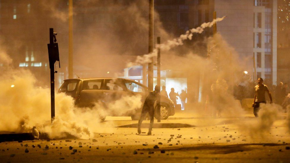 Lebanese demonstrators hurl tear-gas canisters back at riot police during clashes in the capital Beirut