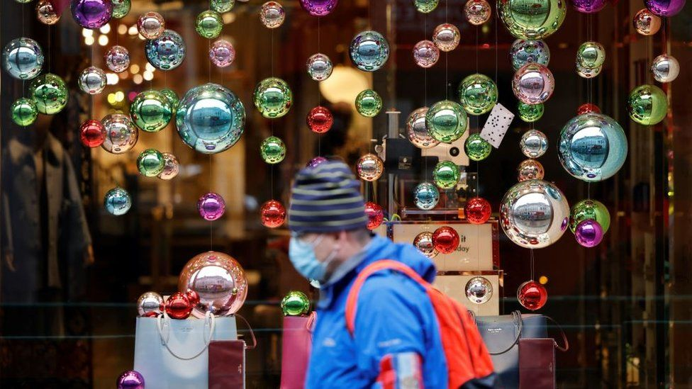 A man wearing a mask walks past a Christmas display