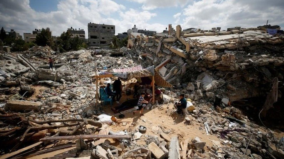 Palestinians sit in a makeshift tent amid the rubble of buildings destroyed in Israeli air strikes in Gaza (23 May 2021)