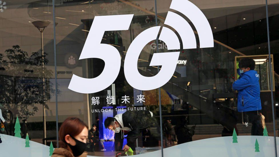 A pedestrian walks past a 5G logo on the window of a Samsung store on February 24, 2020 in Shanghai, China.
