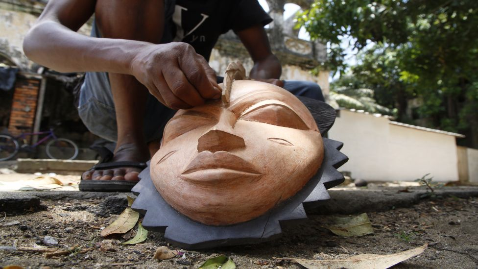 A sculptor carves a mask in his sculpture workshop in Grand-Bassam, Ivory Coast