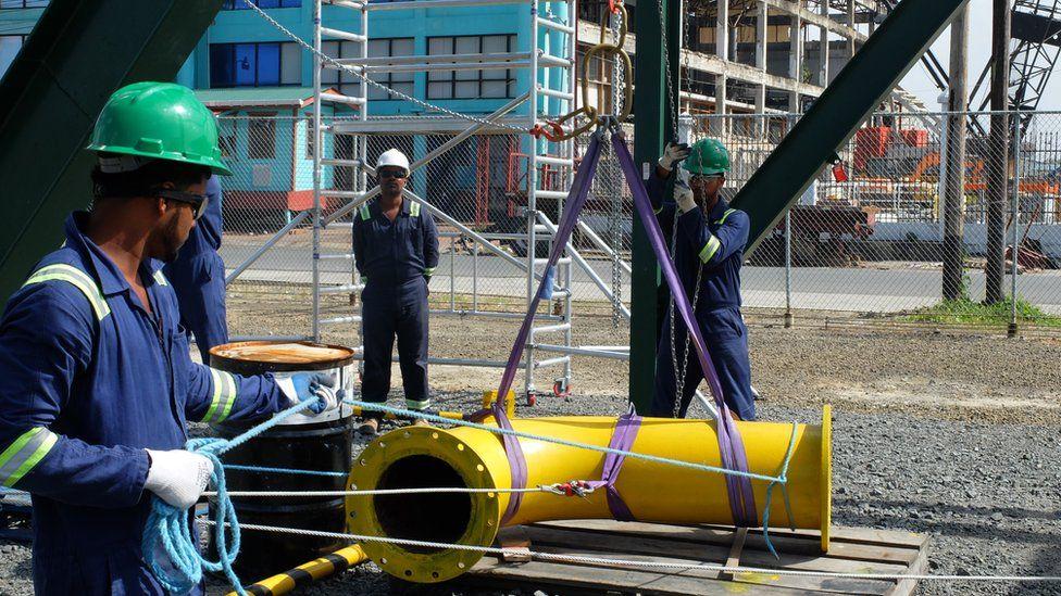 Trabajadores de la industria petrolera instalando equipos en Guyana.
