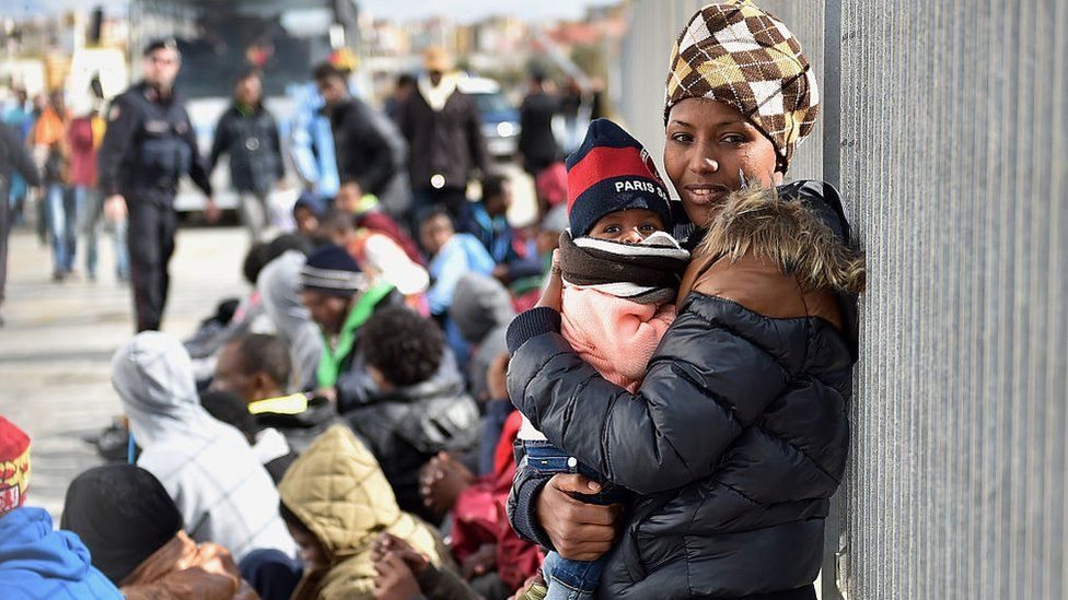 Immigrants wait for a ferry in Lampedusa, southern Italy
