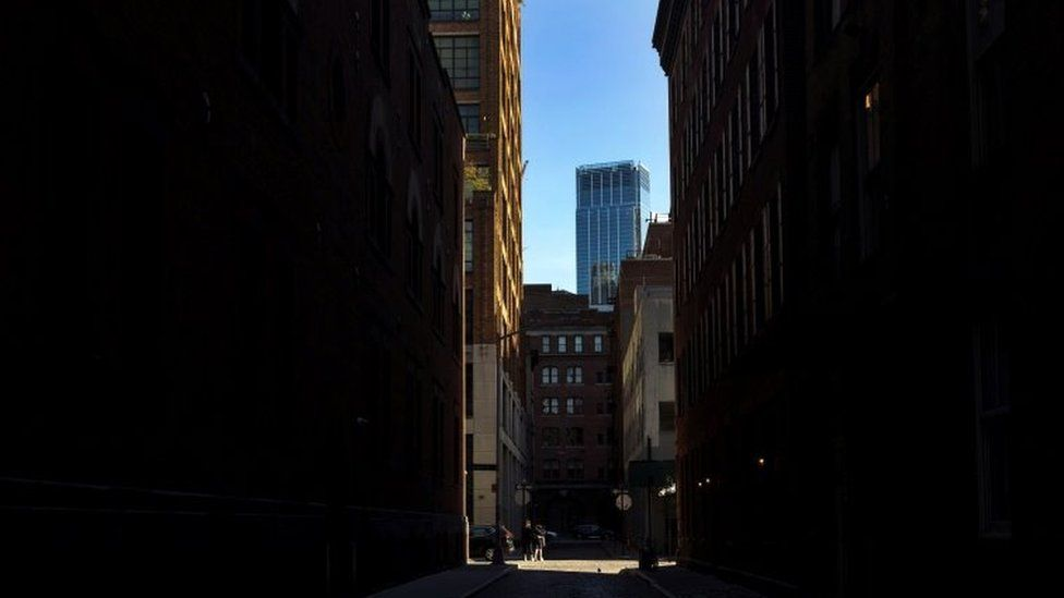 A mother and son walk down an empty Collister Street in Tribeca