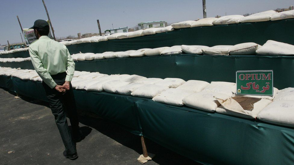 Image shows an Iranian policeman guarding 3,000kg (6,600lb) of opium seized from drug smugglers.