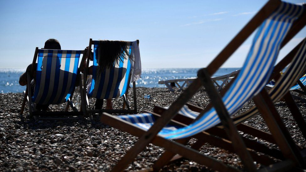 Beachgoers enjoy the hot weather on the seafront at Brighton