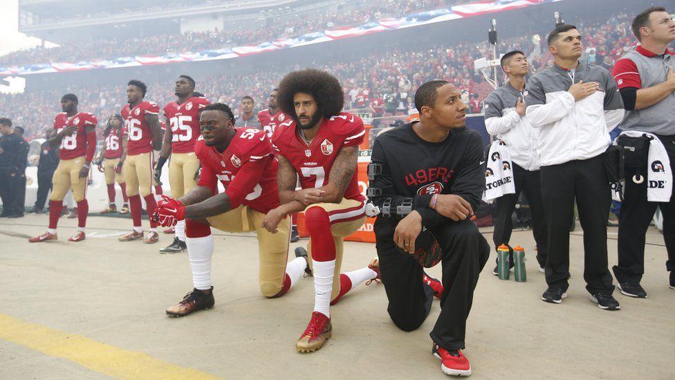 Eli Harold, Colin Kaepernick and Eric Reid kneel during the American national anthem before a San Francisco 49ers v New York Jets game in December 2016