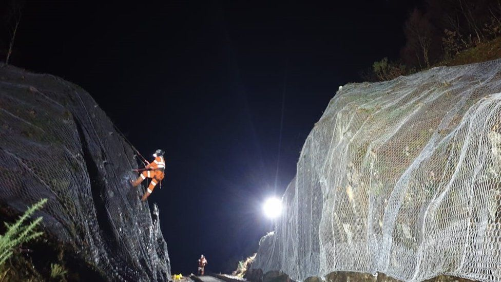 Installing protective netting at a rock cutting