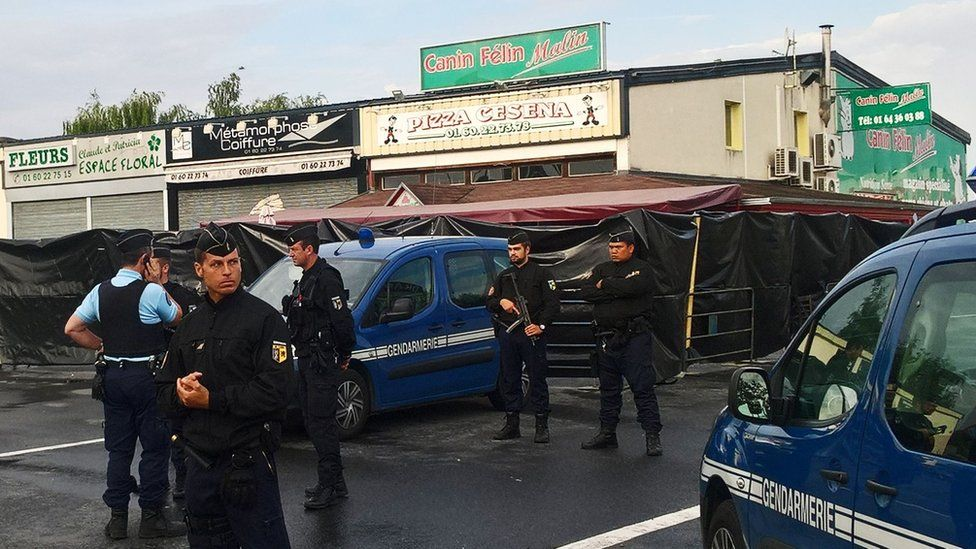 Police officers patrol in front of the scene of a car crash into a pizza restaurant on August 15, 2017 in Sept-Sorts