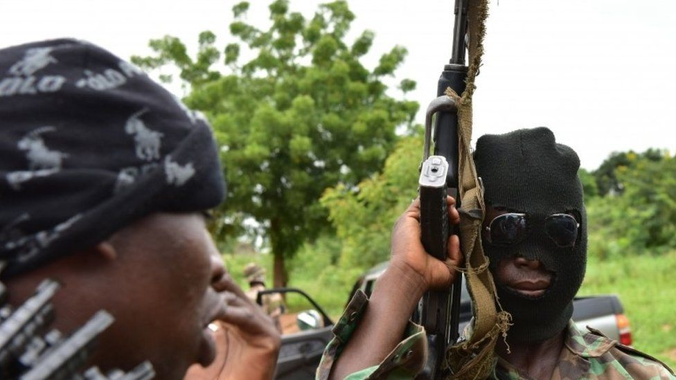 """A mutinous soldier wearing hood holds a weapon inside a military camp in the Ivory Coast""""s central second city Bouake, on May 15, 2017."""
