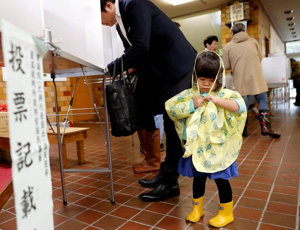 A girl stands next to her father filling out his ballot for a national election at a polling station in Tokyo, Japan October 22, 2017