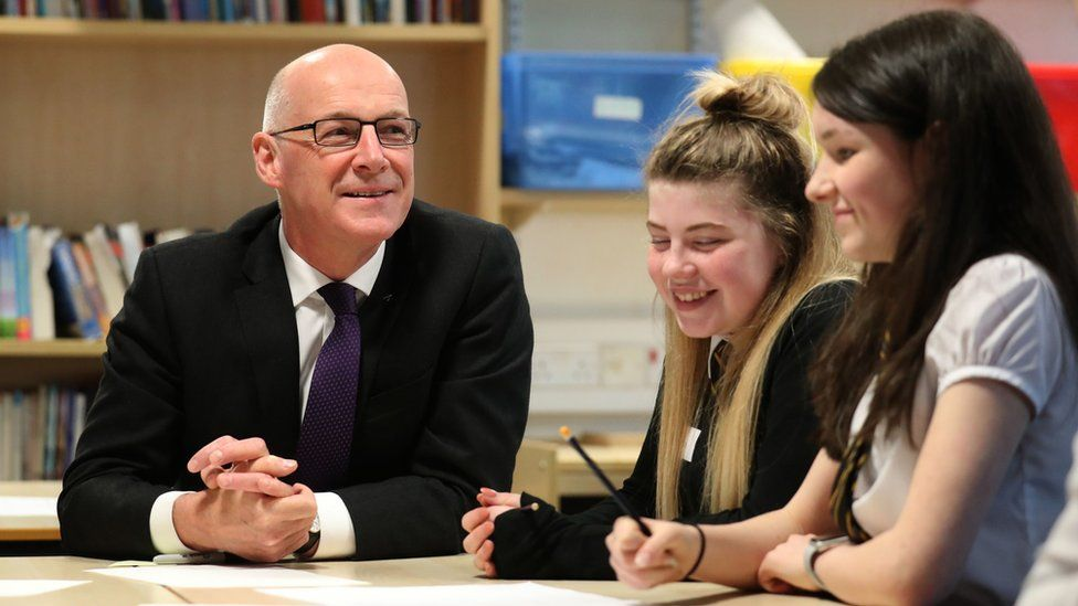 John Swinney sitting talking to pupils in a classroom