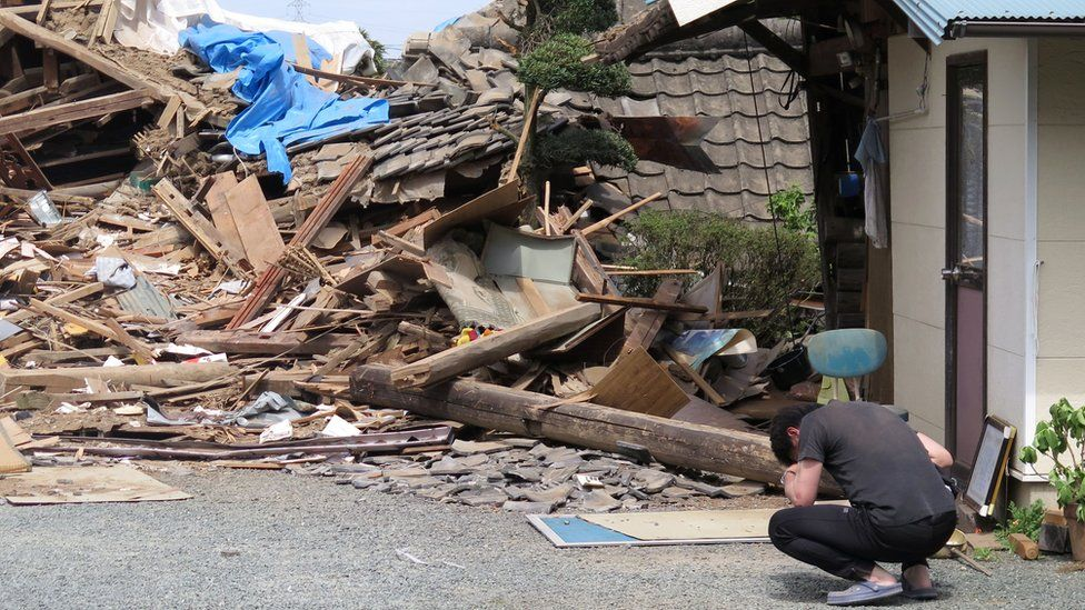 A man in front of a collapsed residence where his mother is trapped after an earthquake in Mashiki, Kumamoto prefecture, southern Japan (16 April 2016)