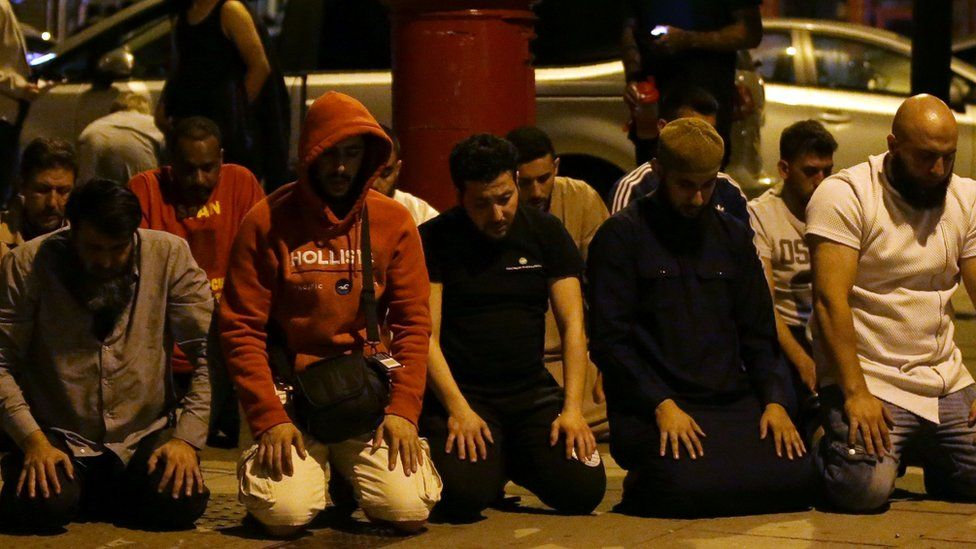 Worshippers pray on the street after the attack