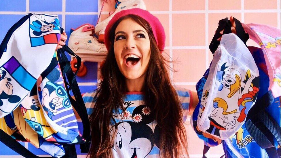 Nikki Millar smiles with her bum bags she creates out of cartoon bed sheets