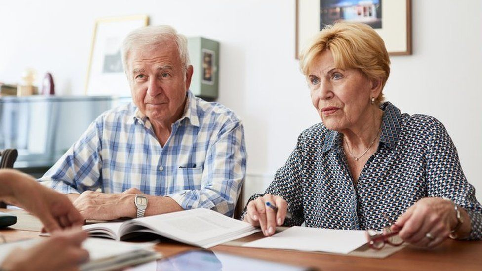 Senior couple meeting with financial consultant at home