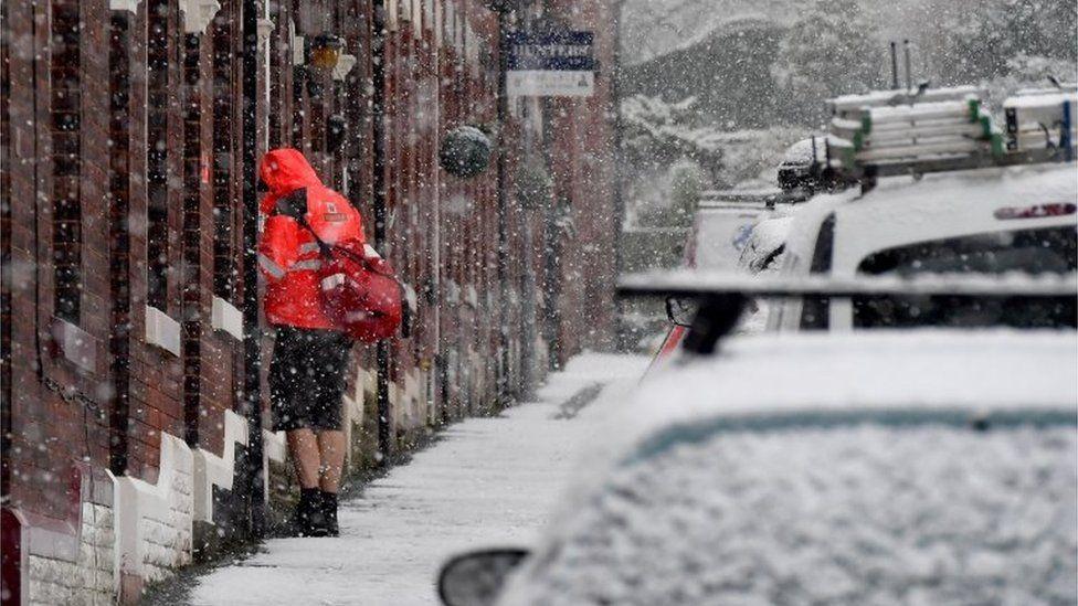 Postman making deliveries in Stalybridge, Greater Manchester