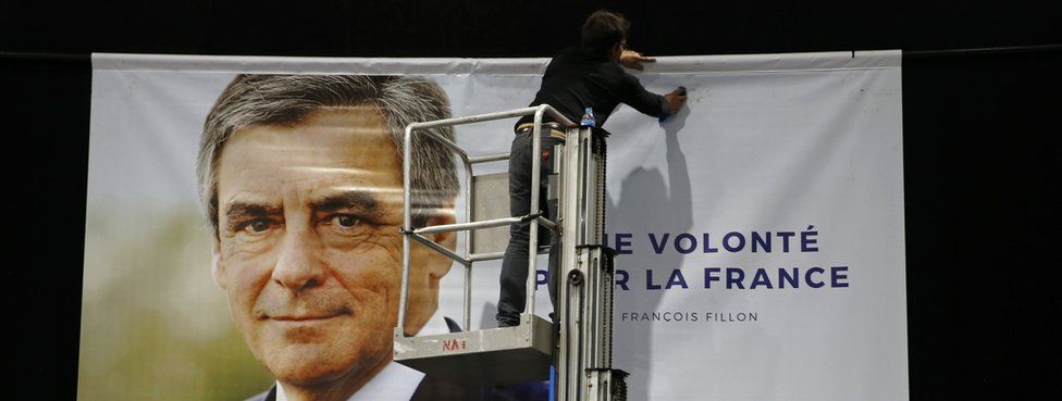 A worker installs a poster to support François Fillon, former French Prime Minister (18 April)