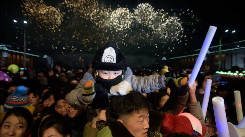 Revellers watch as a fireworks display marks the arrival of the new year following a countdown event on Kim Il Sung Square in Pyongyang on January 1, 2019