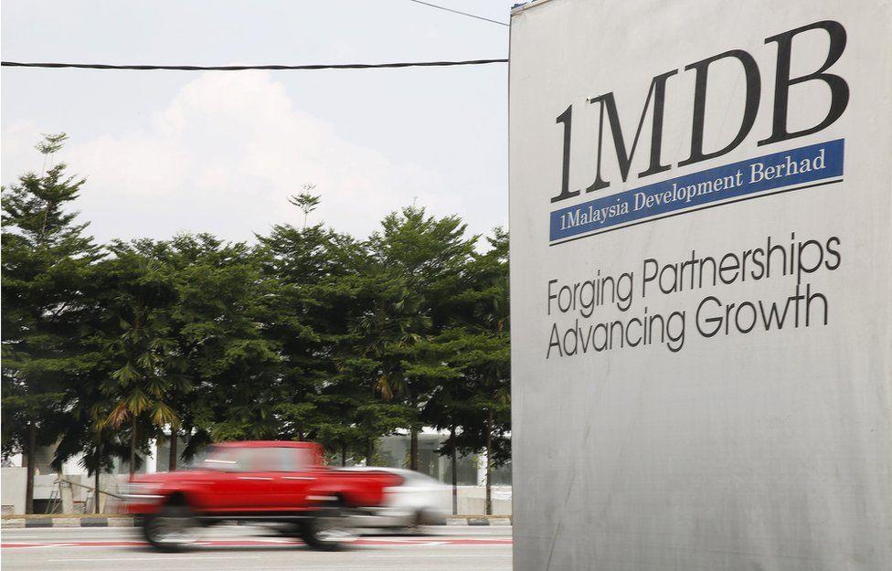 Traffic passes a 1Malaysia Development Berhad (1MDB) billboard in Kuala Lumpur