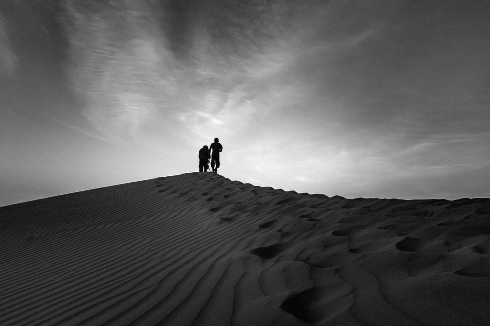 A man walks up a sandy ridge in Egypt