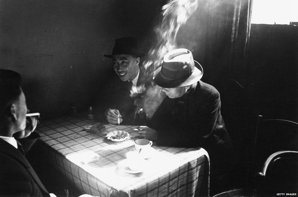 Chinese seamen chatting and smoking at a Chinese hostel in Liverpool, May 1942
