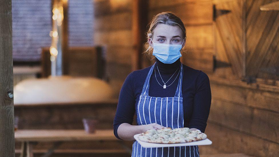 Pizzeria waitress with mask on