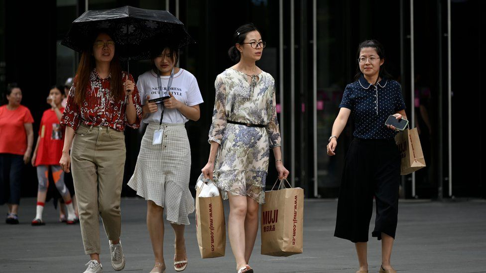 A woman, carrying two shopping bags, walks out of a mall in Beijing on August 14, 2019