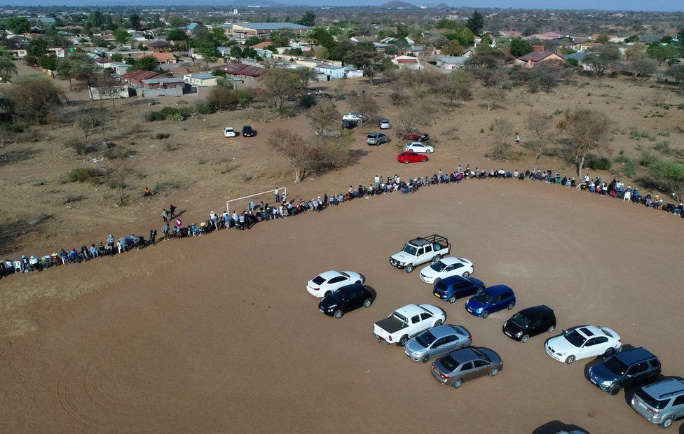 An aerial photograph shows voters waiting in a queue to cast their vote in a polling station in Gaborone on October 23, 2019. - The general election happens in Botswana on October 23, 2019.