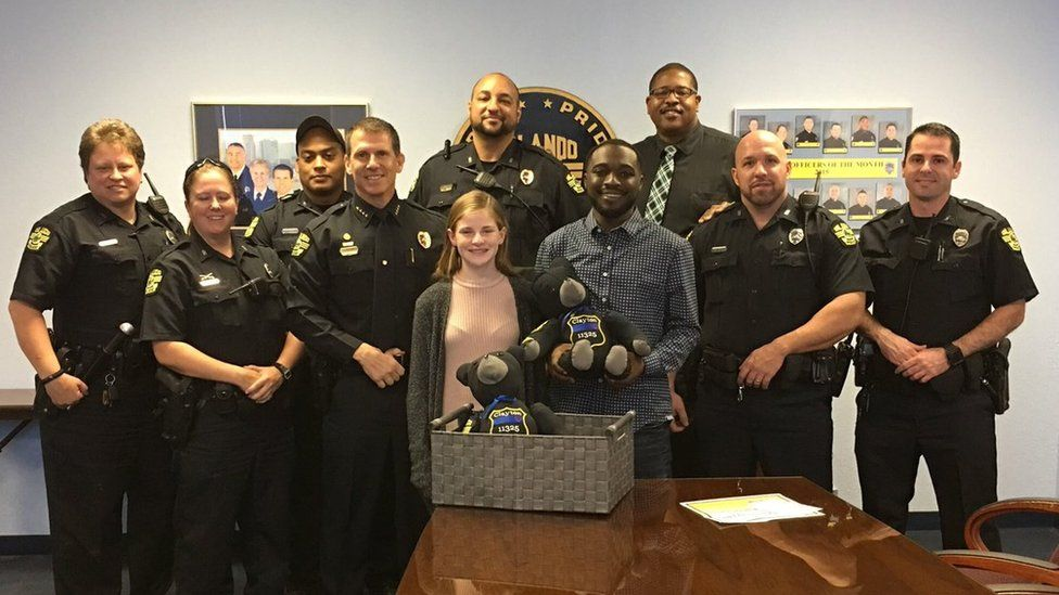 Megan O'Grady presents her Lt. Debra Clayton bear to her son Johnny, along with members of the officer's former squad
