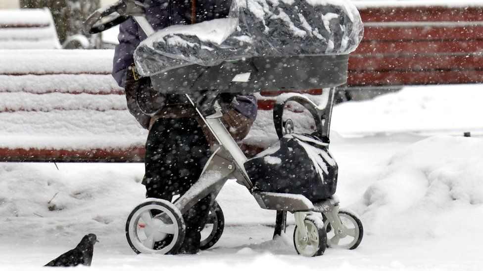 A mother with a buggy in snow (file photo)