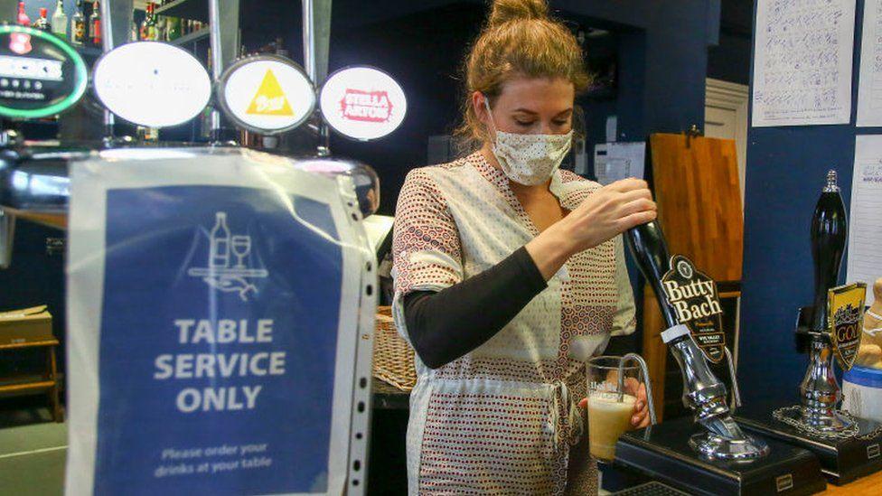 Woman pulling a pint at a pub in Knighton, Powys