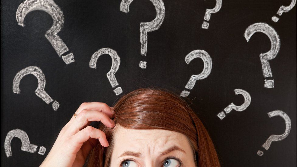 Woman scratching her head in front of question marks