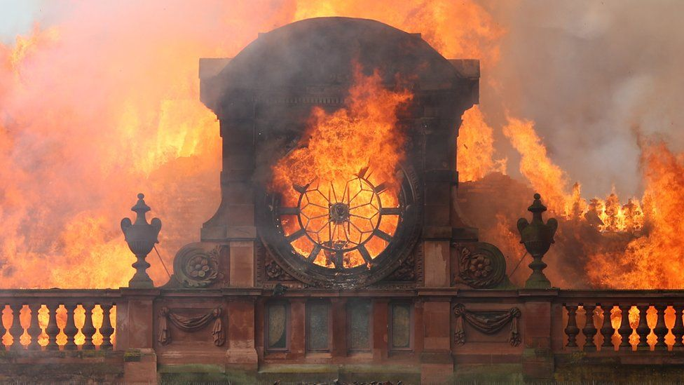 Flames burn through the clock at the top of the Bank Buildings