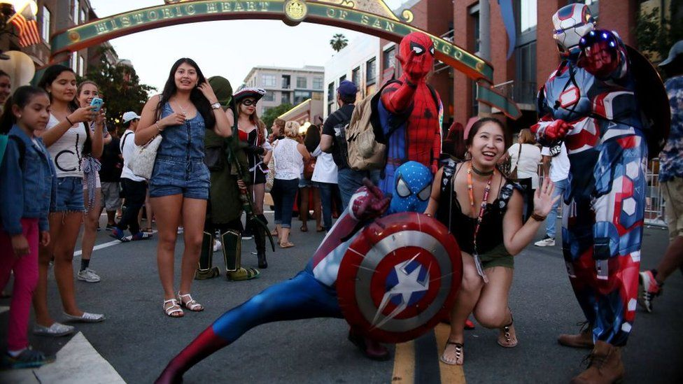 Cosplay characters pose for pictures along 5th Avenue in the Gaslamp Quarter during Comic Con International on July 20, 2017 in San Diego, California